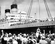 'Mauretania' in port with a large crowd welcoming her passengers, 1955